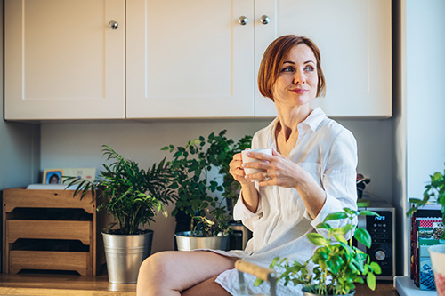A woman is in the kitchen with herbs for PMS