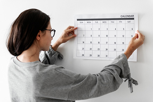 A woman looks at a calendar to track her missing period