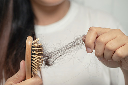 A woman struggling with hair loss in menopause