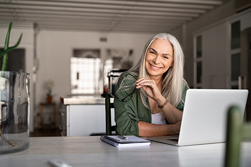 Woman at her computer reading directions for the best place to put estrogen patch