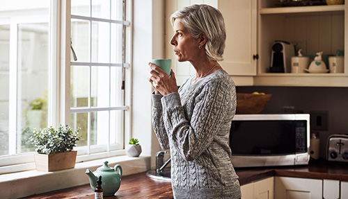 Woman at the window considering the risks of hormone replacement therapy