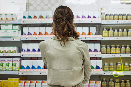 Woman looking at shelves of hormonal management options