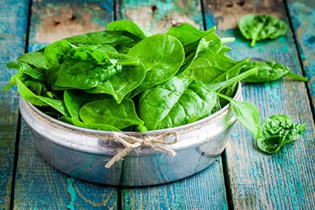 fresh spinach in bowl on wooden table