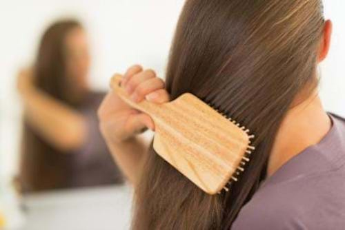 A woman using easy natural tricks to make her thinning hair look fuller