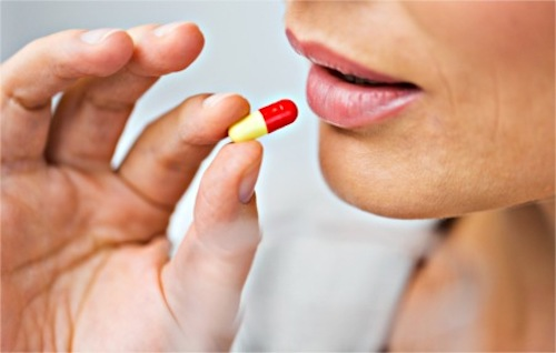 A woman taking an antibiotic