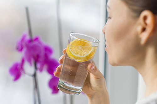 A woman drinking water to relieve her dehydration