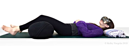 Woman doing Corpse Pose in yoga to reduce stress