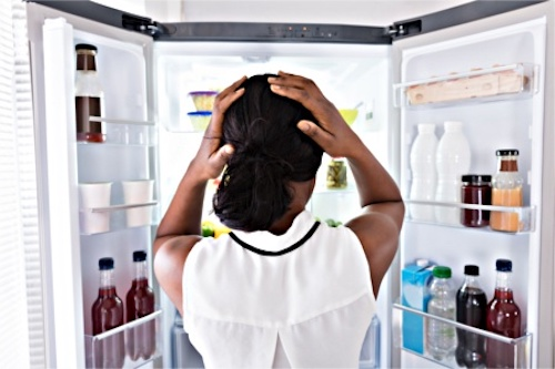 A woman looking into her refrigerator where many nutrients are missing from her diet