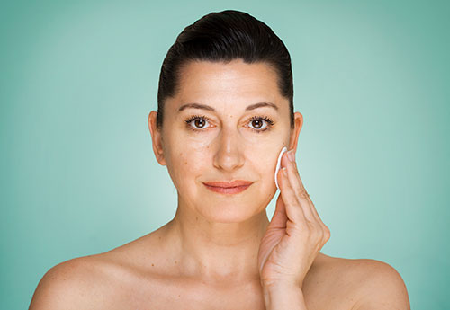 A woman using natural treatments for her hormonal adult acne