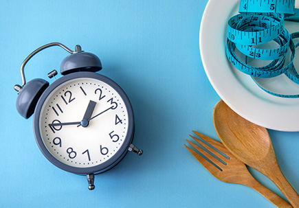 clock next to plate and utensils