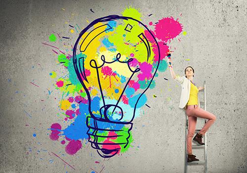woman on ladder creating a big colorful lightbulb as an idea