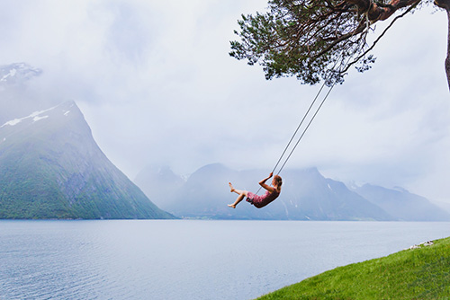 woman swinging in beautiful daydream setting of water and mountains