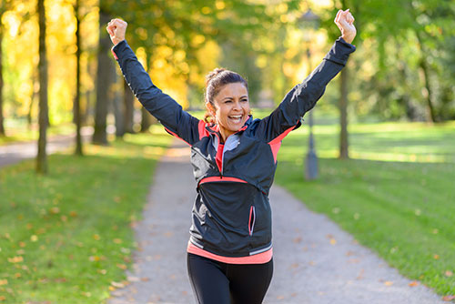 happy and fit woman cheering while running