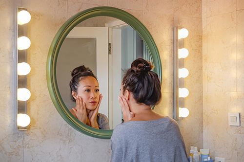 A woman looks in the mirror with concerns about unwanted hair growth