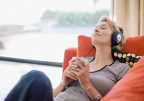 Woman listening to music after learning about her heart palpitation as a hormonal symptom