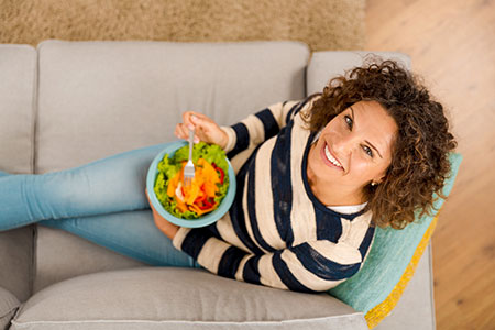 woman eating a salad as part of a healthy diet