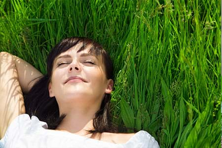 woman relaxing and lying in grass happy to be symptom-free