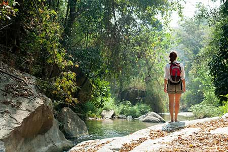 woman standing near river hiking