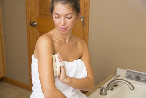 A woman uses dry brushing to improve her skin appearance