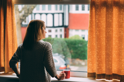 A woman standing indoors looking out a window.