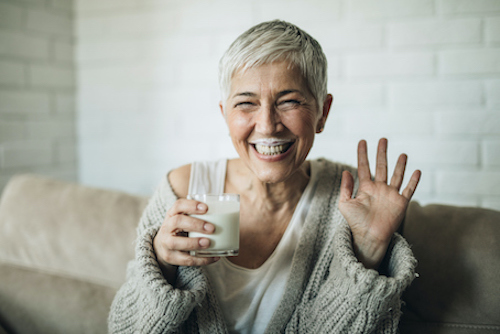 Woman drinking milk to get calcium and Vitamin D for her bones.