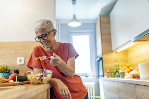 Woman eating food to reduce inflammation and bone loss during menopause.