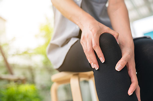 Woman holding her knee in pain with inflammation.