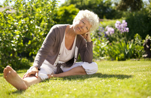 Older woman sitting in the grass thinking about her bone health risk factors.