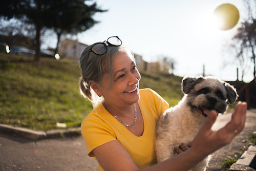 Woman with osteoporosis playing with her dog.