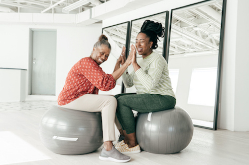 Woman in menopause on exercise ball with her daughter, talking about hormonal balance in menopause.