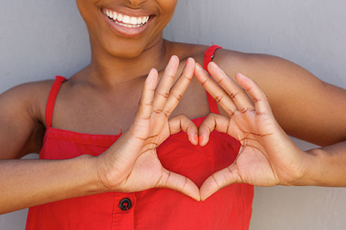 A woman making a heart shape to draw attention to natural heart health for women