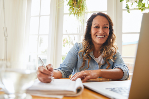 A woman taking notes about the best natural menopause supplements.